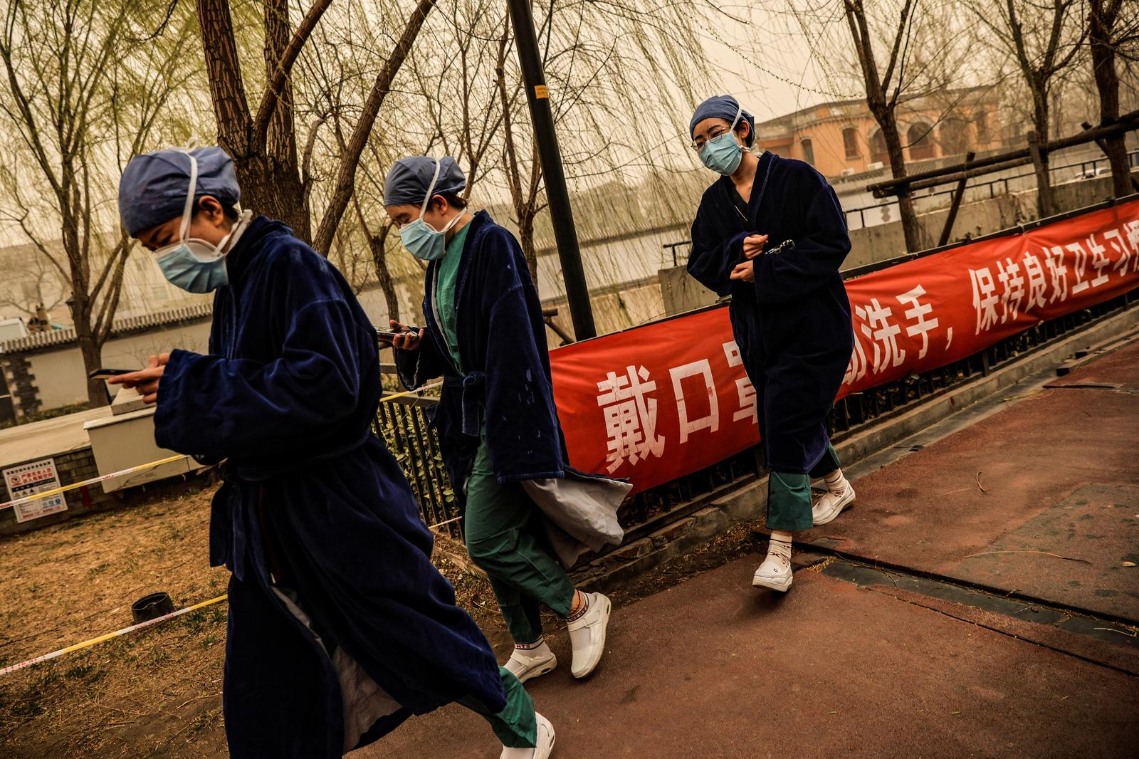 Nurses go about their day during morning rush hour as Beijing, China, is hit by a sandstorm, March 15, 2021. Photo: Reuters