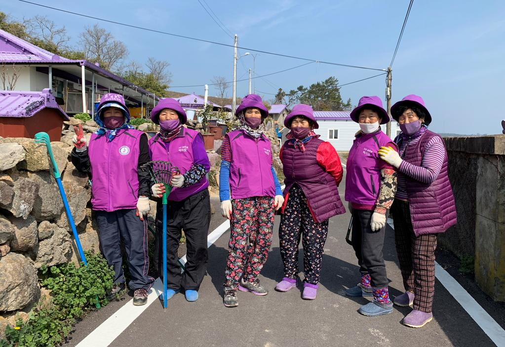 Jung Soon-shim, 88, and other residents dressed in purple clothing pose for a photograph at the Purple Island in Shinan, South Korea, March 8, 2021. Photo: Reuters