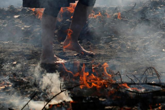 A woman walks across smoldering hot ground at the fire-walking festival, called hiwatari matsuri in Japanese, at Mt.Takao in Tokyo, Japan, March 14, 2021. Photo: Reuters