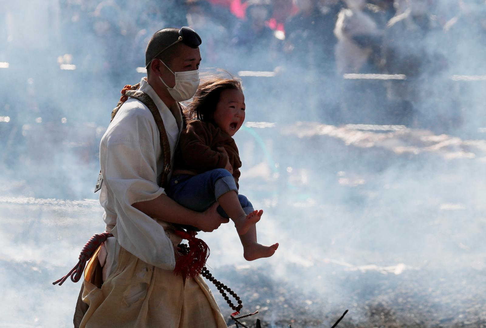 A Buddhist monk wearing a protective mask, amid the coronavirus disease (COVID-19) outbreak, carries a child as he walks across smoldering hot ground at the fire-walking festival, called hiwatari matsuri in Japanese, at Mt.Takao in Tokyo, Japan, March 14, 2021. Photo: Reuters