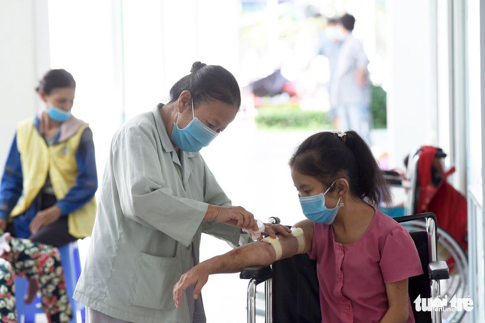 Tran Thi Ut (left) is always on standby to tend to her daughter after the dialysis sessions. Photo: Duyen Phan / Tuoi Tre
