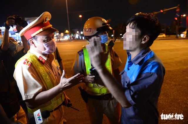 Traffic police officers book a DUI case in Ho Chi Minh City, March 15, 2021. Photo: Tu Trung / Tuoi Tre