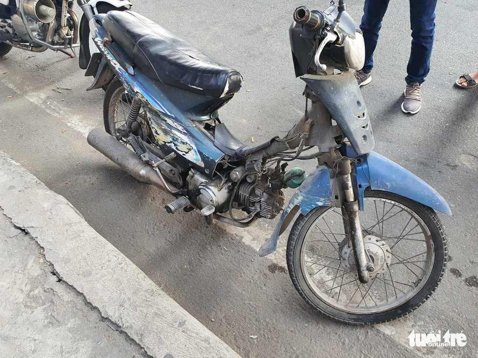 A dilapidated motorcycle is booked by traffic police officers in Ho Chi Minh City, March 15, 2021. Photo: Tu Trung / Tuoi Tre
