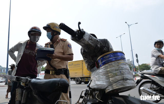 A traffic police officer books a dilapidated motorcycle in Ho Chi Minh City, March 16, 2021. Photo: Tu Trung / Tuoi Tre
